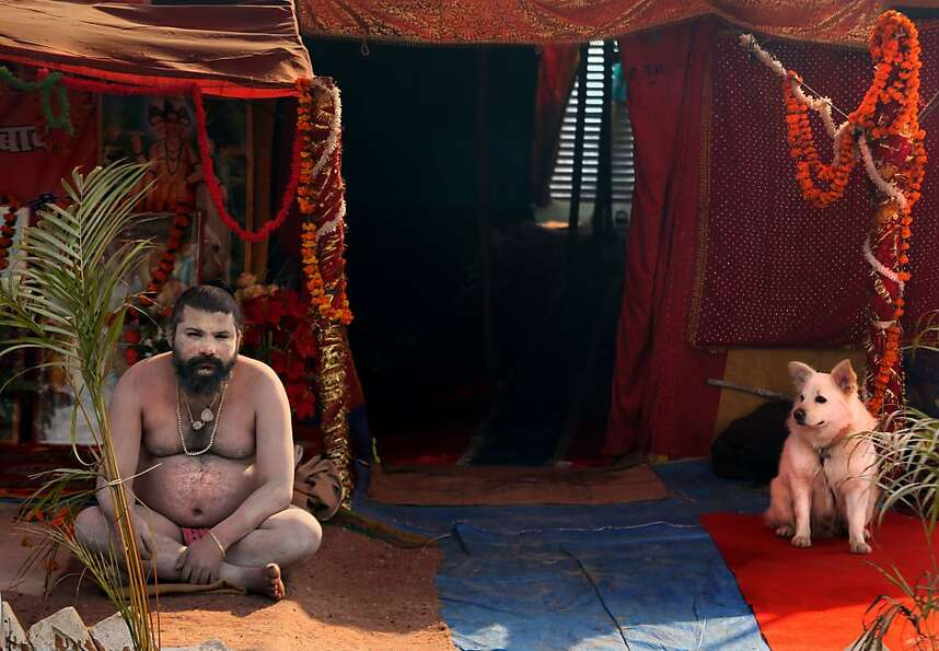 A naked Hindu holy man or a Naga Sadhu and his dog watches as devotees walk past his tent at Sangam,