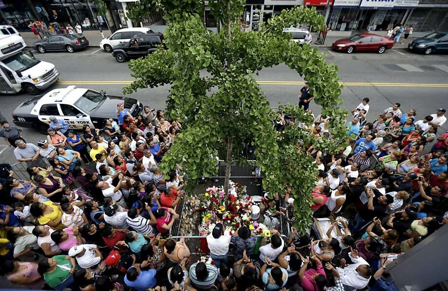 In this July 15, 2012 photo, people gather around a tree where believers say the image of the Virgin of Guadalupe appeared on the tree's trunk as a Mariachi band serenades the Virgin in West New York, N.J.  Believers, who pray in front of the tree nightly, say the outline of the Virgin of Guadalupe appeared on the tree on July 5, 2012, and they are collecting money in hopes of building a glass shrine to protect the image. (AP Photo/Julio Cortez) Photo: Julio Cortez, Associated Press