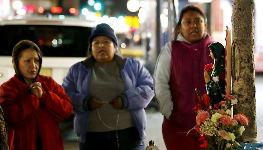 Eva Copacicla, left, Enriqueta Morales, center, and Julieta Baez pray in front of a tree where believers say an image of the Virgin of Guadalupe appeared in West New York,N.J., late Monday, Jan. 14, 2013. Believers, who pray in front of the tree nightly, say the outline of the Virgin of Guadalupe appeared on the tree on July 5, 2012, and they are collecting money in hopes of building a glass shrine to protect the image. (AP Photo/Julio Cortez) Photo: Julio Cortez, Associated Press