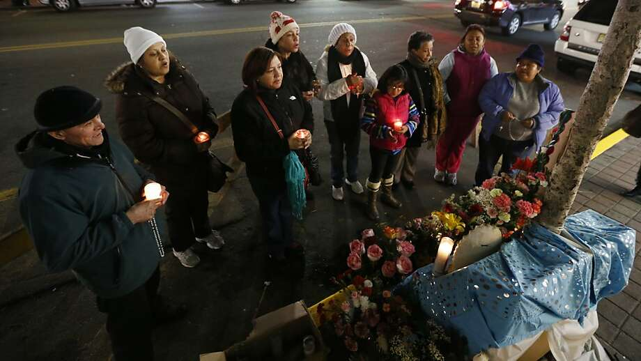 People pray the rosary in front of a tree where believers say an image of the Virgin of Guadalupe appeared in West New York, N.J., late Monday, Jan. 14, 2013.  Believers, who pray in front of the tree nightly, say the outline of the Virgin of Guadalupe appeared on the tree's trunk on July 5, 2012, and they are collecting money in hopes of building a glass shrine to protect the image. (AP Photo/Julio Cortez) Photo: Julio Cortez, Associated Press