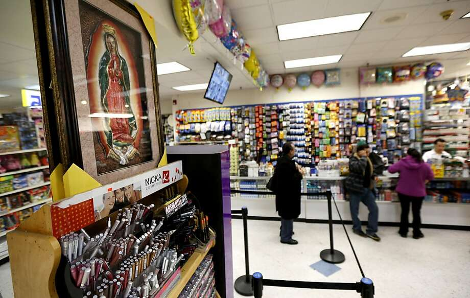 A framed image of the Virgin of Guadalupe is displayed for sale at a convenience store in West New York, N.J., late Monday, Jan. 14, 2013.  Across the street from the store, believers pray nightly in front of a tree where they say the outline of the Virgin of Guadalupe appeared on the tree's trunk on July 5, 2012, and they are collecting money in hopes of building a glass shrine to protect the image. (AP Photo/Julio Cortez) Photo: Julio Cortez, Associated Press
