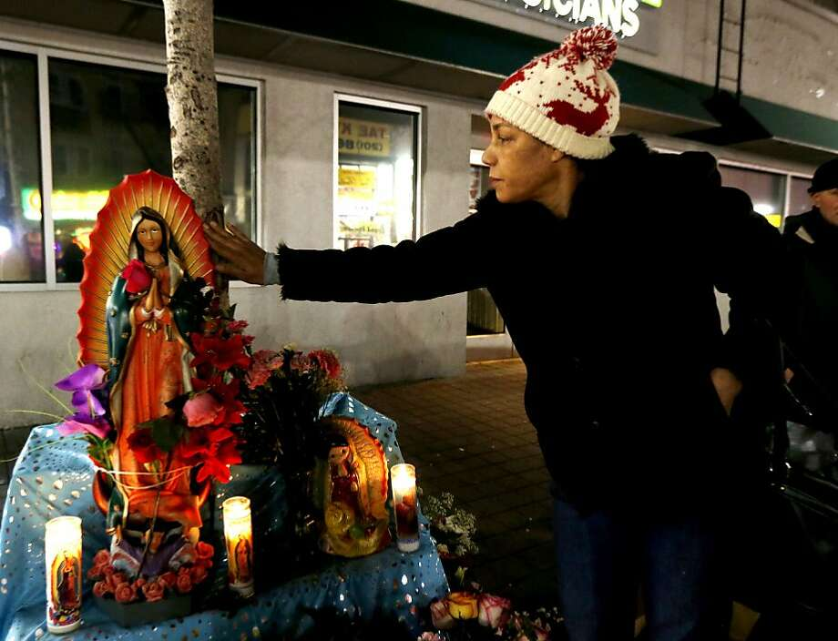 Marta Trinidad touches the spot on a tree trunk where believers say the image of the Virgin of Guadalupe appeared, as she arrives to pray the rosary with others in West New York, N.J., late Monday, Jan. 14, 2013. Believers, who pray in front of the tree nightly, say the outline of the Virgin of Guadalupe appeared on the tree on July 5, 2012, and they are collecting money in hopes of building a glass shrine to protect the image. (AP Photo/Julio Cortez) Photo: Julio Cortez, Associated Press