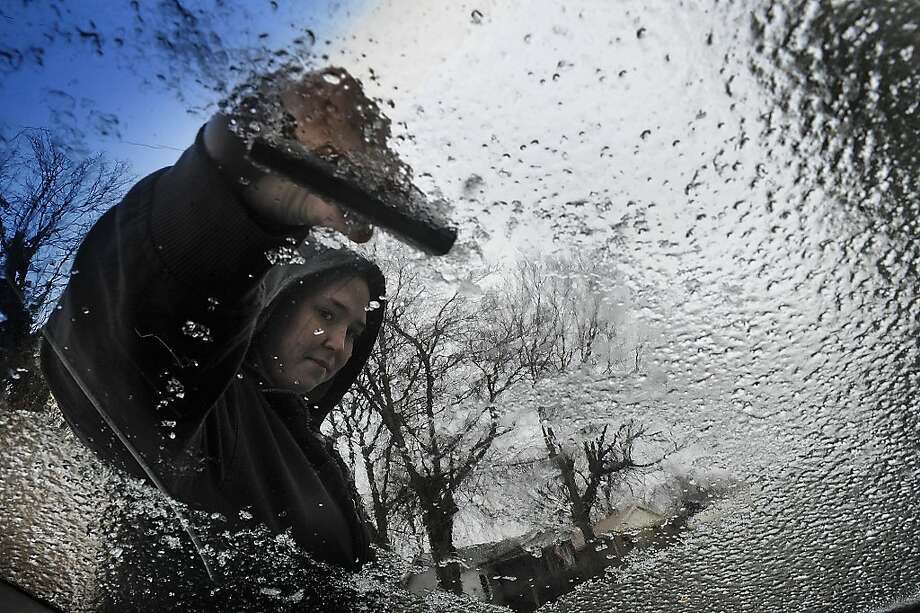 Brooke Giles scrapes ice of her winshield of her car as freezing temperatures hit middle Tennessee, Tuesday, Jan. 15, 2013, in Nashville, Tenn. (AP Photo/The Tennessean, John Partipilo)  NO SALES Photo: John Partipilo, Associated Press