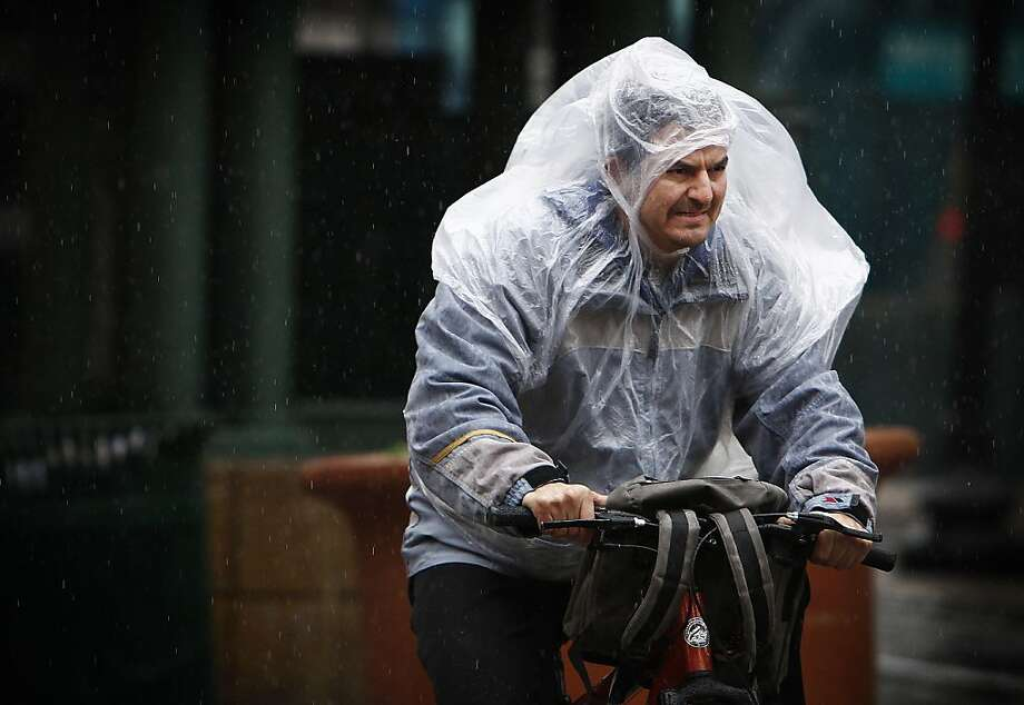Jesus Lozano takes precautions from the cold windy rain while riding his bike on N. Main in Downtown Memphis, Tenn. Tuesday Jan. 15, 2013. (AP Photo/The Commercial Appeal, Mark Weber) Photo: Nikki Boertman, Associated Press