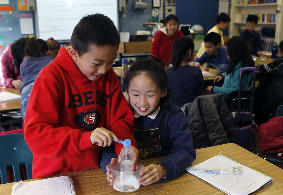 Otto Gin and Anita Liu pours salt into water for a science experiment in Melissa Thormahlen's 4th and 5th grade class at John Yehall Chin Elementary School in San Francisco, Calif. on Tuesday, Jan. 15, 2013. Photo: Paul Chinn, The Chronicle