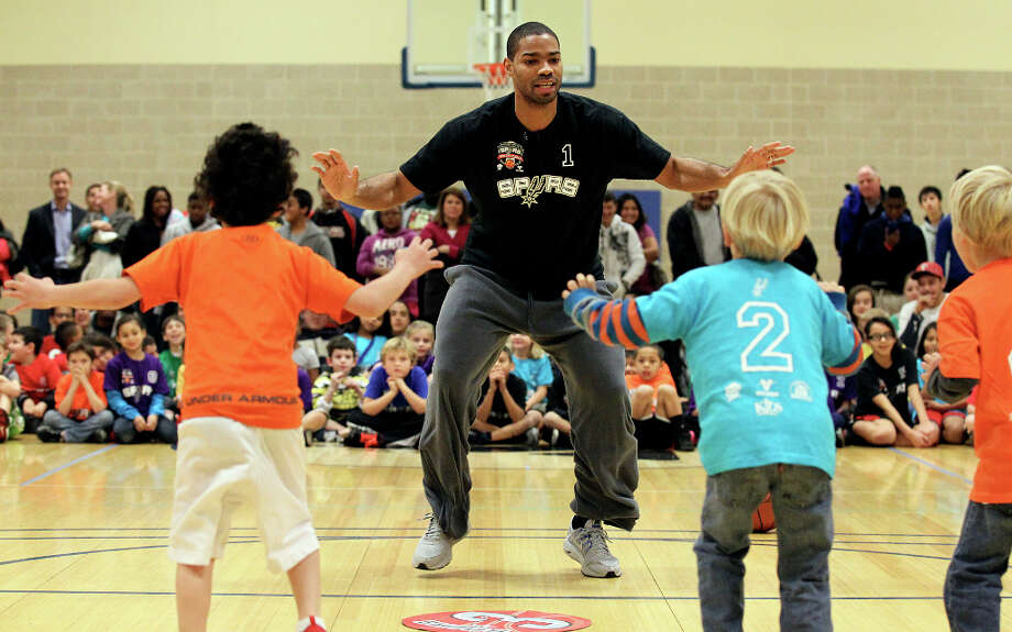 Spurs guard Gary Neal (center) performs a drill with a group of children at the Spurs Youth Basketball League Kids Clinic at the Walzem YMCA on Tuesday, Jan. 15, 2013. About a hundred kids came out to interact with Neal and Spurs Assistant Coach Brett Brown. The clinic stressed the importance of making good decisions and staying in school while also teaching the kids a few basketball fundamentals. Photo: Kin Man Hui, San Antonio Express-News / © 2012 San Antonio Express-News