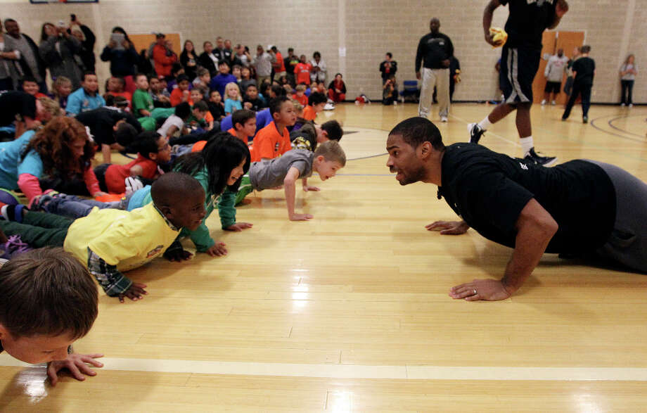 Spurs guard Gary Neal (right) does push-ups with kids at the Spurs Youth Basketball League Kids Clinic at the Walzem YMCA on Tuesday, Jan. 15, 2013. About a hundred kids came out to interact with Neal and Spurs Assistant Coach Brett Brown. The clinic stressed the importance of making good decisions and staying in school while also teaching the kids a few basketball fundamentals. Photo: Kin Man Hui, San Antonio Express-News / © 2012 San Antonio Express-News