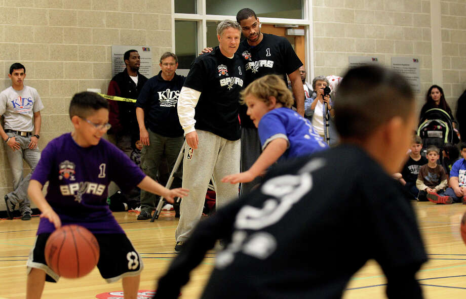 Spurs guard Gary Neal (right) and assistant coach Brett Brown observe a group of children doing basketball drills at the Spurs Youth Basketball League Kids Clinic at the Walzem YMCA on Tuesday, Jan. 15, 2013. About a hundred kids came out to interact with Neal and Brown. The clinic stressed the importance of making good decisions and staying in school while also teaching the kids a few basketball fundamentals. Photo: Kin Man Hui, San Antonio Express-News / © 2012 San Antonio Express-News
