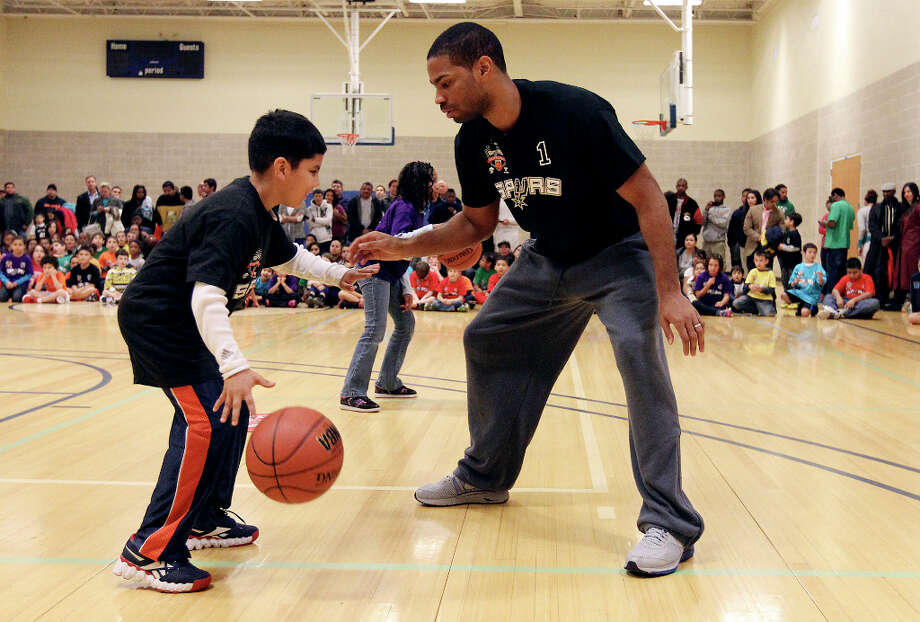 Spurs guard Gary Neal helps Oscar Gonzalez, 8, with a drill at the Spurs Youth Basketball League Kids Clinic at the Walzem YMCA on Tuesday, Jan. 15, 2013. About a hundred kids came out to interact with Neal and Spurs Assistant Coach Brett Brown. The clinic stressed the importance of making good decisions and staying in school while also teaching the kids a few basketball fundamentals. Photo: Kin Man Hui, San Antonio Express-News / © 2012 San Antonio Express-News