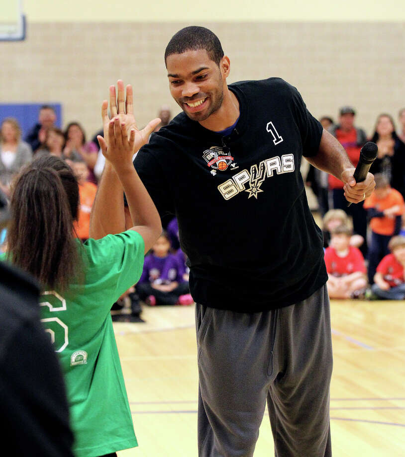 Spurs guard Gary Neal (right) offers a high-five to Mikayla Whitby, 10, after a basketball drill competition during the Spurs Youth Basketball League Kids Clinic at the Walzem YMCA on Tuesday, Jan. 15, 2013. About a hundred kids came out to interact with Neal and Spurs Assistant Coach Brett Brown. The clinic stressed the importance of making good decisions and staying in school while also teaching the kids a few basketball fundamentals. Photo: Kin Man Hui, San Antonio Express-News / © 2012 San Antonio Express-News
