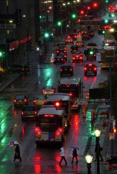 Pedestrians cross Texas Avenue as rain sprinkles Tuesday, Jan. 15, 2013, in Houston. Photo: Cody Duty, Houston Chronicle / © 2012 Houston Chronicle
