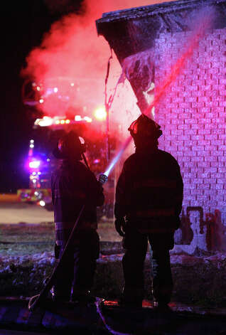 San Antonio firefighters spray water on a single story home Wednesday January 16, 2013 at the corner of Elmendorf and Woodlawn. Fire Captain Roger Lopez said the fire was probably caused by a malfunctioning heater that was being used to keep some pets warm. Flames erupted at the home about 5:20 a.m. and caused about $200,000 in damage. There were no injuries and the pets appeared to make it out of the home safely. Photo: JOHN DAVENPORT, San Antonio Express-News / © San Antonio Express-News