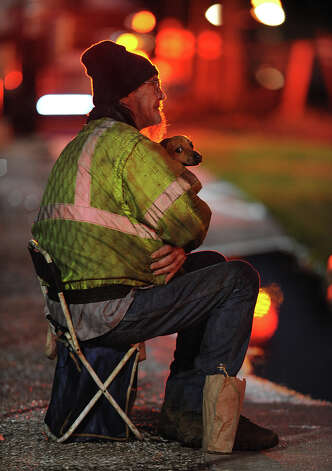 Gerald Bryant and Harley, a mutt, watch Beaumont firefighters extinguish a fire Tuesday in the Old Town home that he lived in. Bryant, his wife and a third person exscaped the fire when a neighbor banged on the window to announce seeing smoke. An investigation to find the source of the fire is underway.  Photo taken Tuesday, January 15, 2013 Guiseppe Barranco/The Enterprise Photo: Guiseppe Barranco, STAFF PHOTOGRAPHER / The Beaumont Enterprise