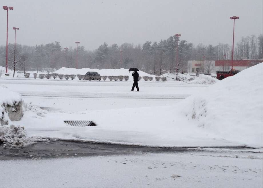 A man uses an umbrella to shield himself from the wet snow as he makes his way across the Target parking lot on Wednesday, Jan. 16, 2013 in Albany, NY. (Paul Buckowski / Times Union) Photo: (Paul Buckowski / Times Union)