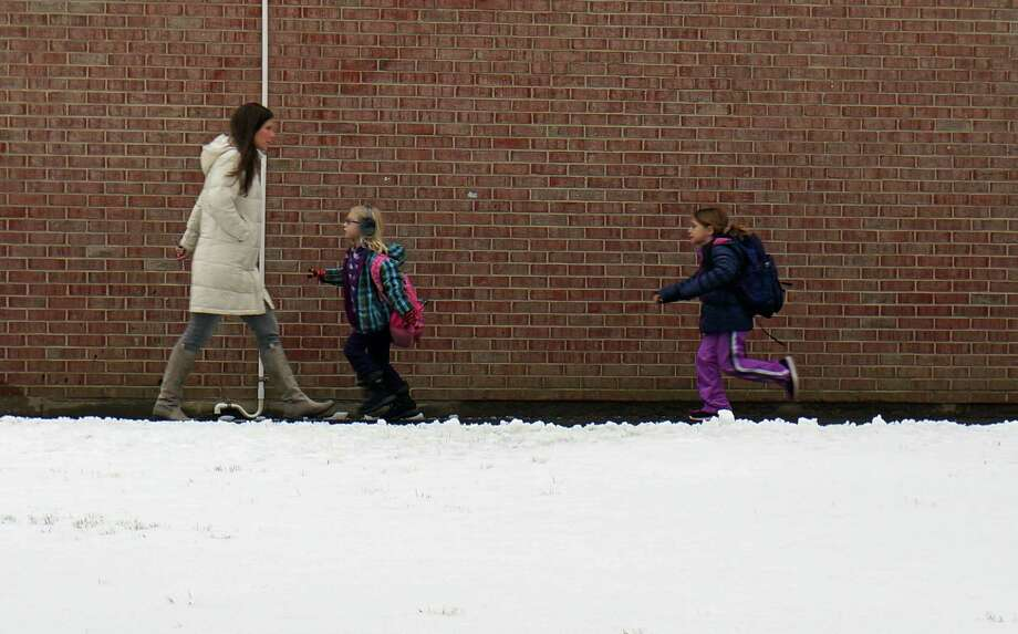 Sherman School students run to their class after a snowstorm prompted a delayed opening Wednesday. Photo: Genevieve Reilly / Fairfield Citizen
