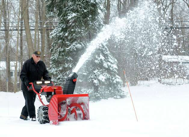 Chuck Tredennick uses a snowblower to clean off his Cross Highway driveway in Redding, Conn. on Wednesday, Jan. 16, 2013.  An overnight snowfall blanketed the area making for a busy morning commute for many. Photo: Cathy Zuraw / The News-Times