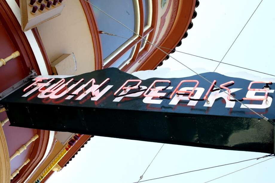 The neon sign for the famed Twin Peaks bar showing the Victorian architecture of the building.