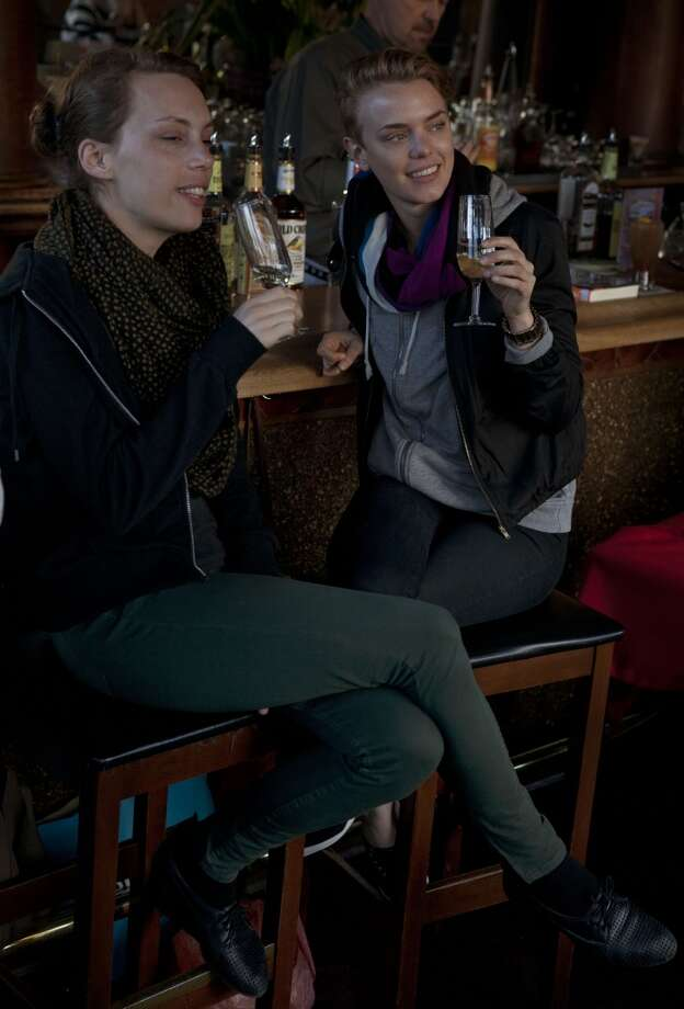 Couple Emma Soderstrom (left) and Carin Goransson (right) visiting from Sweden looking out the windows while having white wine at Twin Peaks Tavern