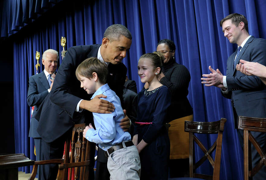 President Barack Obama, accompanied by Vice President Joe Biden, left, hugs eight-year-old letter wr