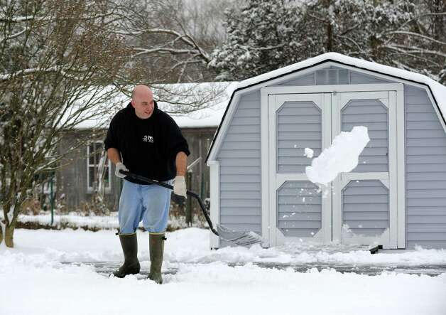 Bryan Terzian shovels the walkways on a home on Fleetwood Ave. in Bethel, Conn. on Wednesday, Jan. 16, 2013. An overnight snowfall blanketed the area making for a messy morning commute. Photo: Cathy Zuraw / The News-Times