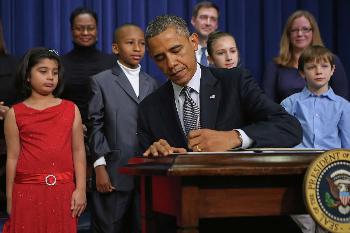 U.S. President Barack Obama signs a series of executive orders about the administration's new gun law proposals as children who wrote letters to the White House about gun violence, Hinna Zeejah, Taejah Goode, Julia Stokes and Grant Fritz, look on in the Eisenhower Executive Office building January 16, 2013 in Washington, DC. One month after a massacre that left 20 school children and 6 adults dead in Newtown, Connecticut, the president unveiled a package of gun control proposals that include universal background checks and bans on assault weapons and high-capacity magazines.