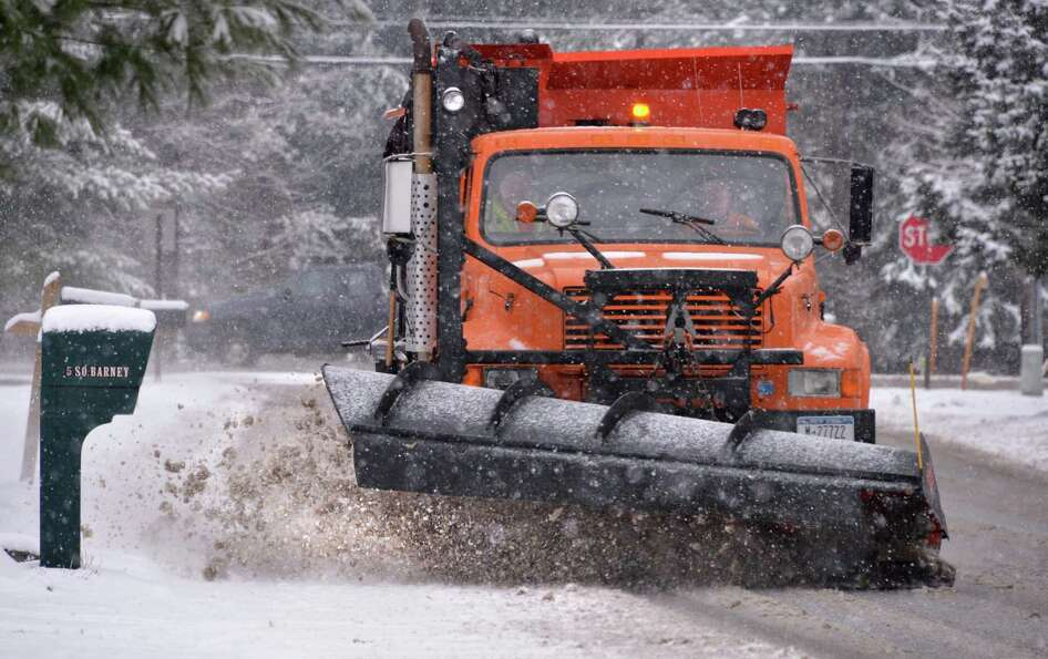 A Clifton Park town snowplow works to clear South Barney Road Wednesday morning, Jan. 16, 2013, in C