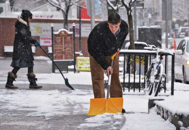 Chris Hayden shovels snow from the sidewalk on Broadway Wednesday morning, Jan. 16, 2013, in Saratoga Springs, N.Y. (John Carl D'Annibale / Times Union) Photo: John Carl D'Annibale / 00020789A