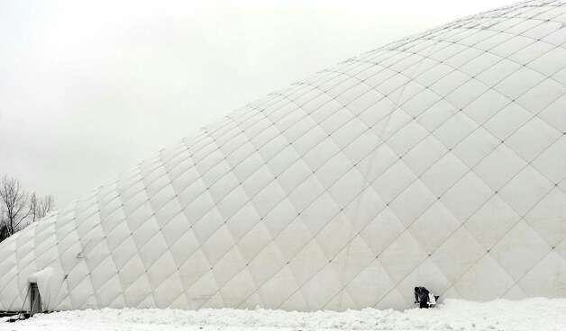 Rigo Guerra shovels along the base of the Danbury Sports Dome,a large air-supported complex under construction on off Shelter Rock Lane in Danbury, Conn. on Wednesday, Jan. 16, 2013. An overnight snowfall blanketed the area making for a messy morning commute across the state. Photo: Cathy Zuraw / The News-Times