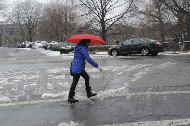 A woman rush along Greenwich Avenue near the snow in Greenwich, Conn., Jan. 16, 2013 Photo: Helen Neafsey / Greenwich Time