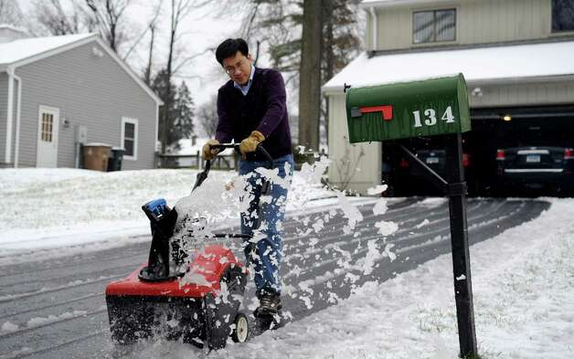 Darwin Shen uses a snowblower to clear his Stamford driveway after slushy snow blanketed the city on Wednesday, January 16, 2012. Photo: Lindsay Perry / Stamford Advocate