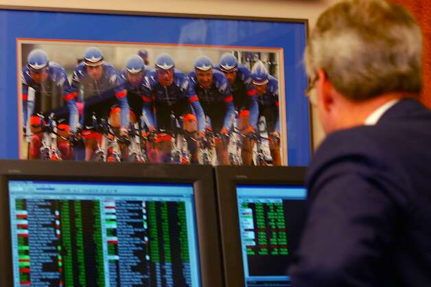 Thom Weisel checks the stock market near a photo of Lance Armstrong's team on Sept. 4, 2002. Thom Weisel, CEO of  the SF investment firm Thomas Weisel Partners has his office wall full of Lance Armstrong photos including 3 framed yellow jerseys presented to him by his friend Lance Armstrong. Photo: Michael Maloney, The Chronicle
