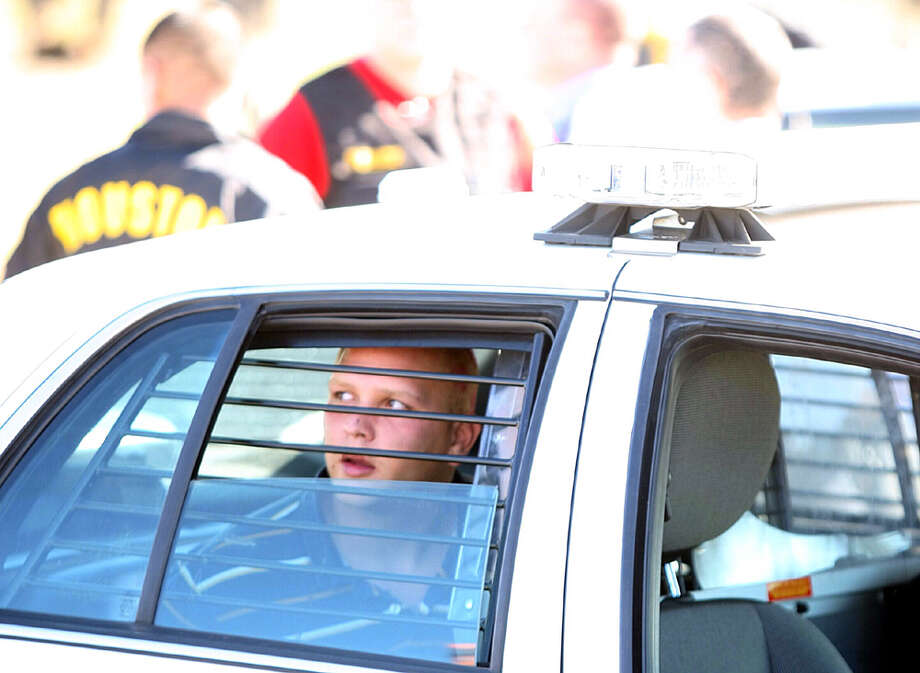 Bank robbery suspect sits in a police car after leading HPD on a chase, at Beech-White park in SE Houston.Wednesday, Jan. 16, 2013. Photo: Nick De La Torre / Houston Chronicle