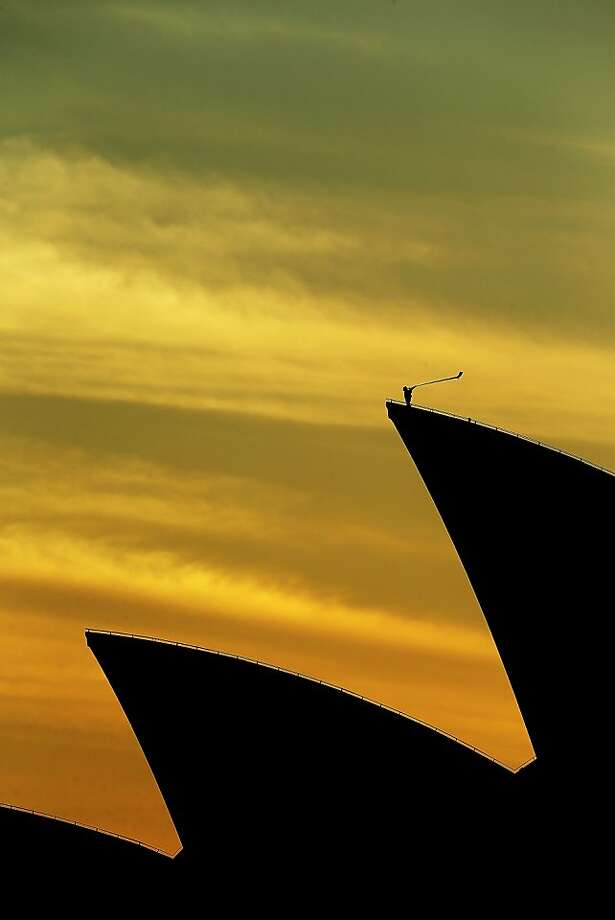 Arkady Shilkloper hits a high note on his 10-foot-long alphorn atop the Sydney Opera House as part of the Sydney Festival. Photo: Mark Metcalfe, Getty Images