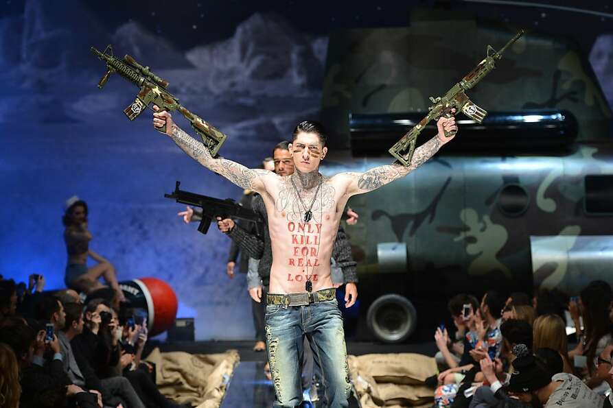 If gun models are outlawed, only models will have guns: An armed and inked model walks the ru