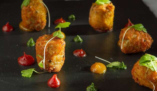 Mini crab cakes are served with dabs of red and green sauces, sliced cornichons and parsley. Photo: John Storey, Special To The Chronicle
