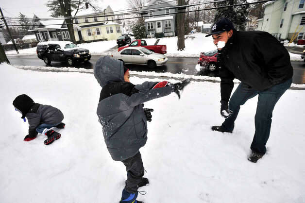 Emmanuel Cueto, 4, center, throws a snowball at his dad, Gary, as Emmanuel's brother, Ezequiel, 3, readies another snowball in front of their home on Westville Avenue in Danbury on Wednesday, Jan. 16, 2013. Photo: Jason Rearick / The News-Times