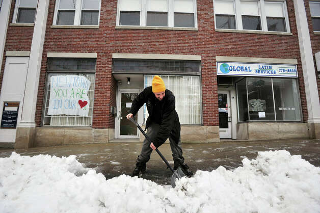 Erik Carr, a maintenance worker with CityCenter Danbury, clears snow from in front of businesses on West Street in Danbury on Wednesday, Jan. 16, 2013. The Connecticut Weather Center reported Danbury received almost four inches of snow. Photo: Jason Rearick / The News-Times
