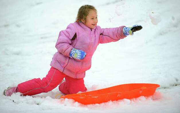 Paige Fortin, 7, of Ansonia, takes a break from sledding to thrown snowballs behind Derby Middle School Wednesday, Jan. 16, 2013 in Derby, Conn. Photo: Autumn Driscoll / Connecticut Post