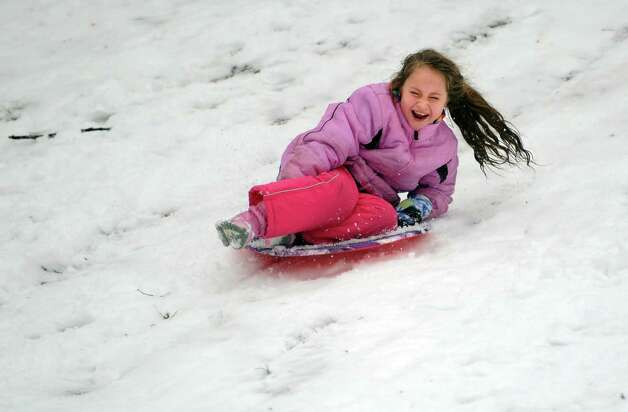 Seven-year-old Paige Fortin, of Ansonia, sleds down the hill behind Derby Middle School Wednesday, Jan. 16, 2013 in Derby, Conn. Photo: Autumn Driscoll / Connecticut Post