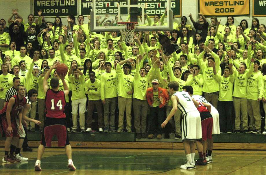 "Jeff Nabozna of the Rebels does his best to focus on his free throw as hundreds of Green Wave students - all wearing ""The Tsunami"" T-shirts - do their very best to distract him during the final moments of New Milford High School boys' basketball game vs. New Fairfield, Jan. 11, 2013 at NMHS. Photo: Norm Cummings"