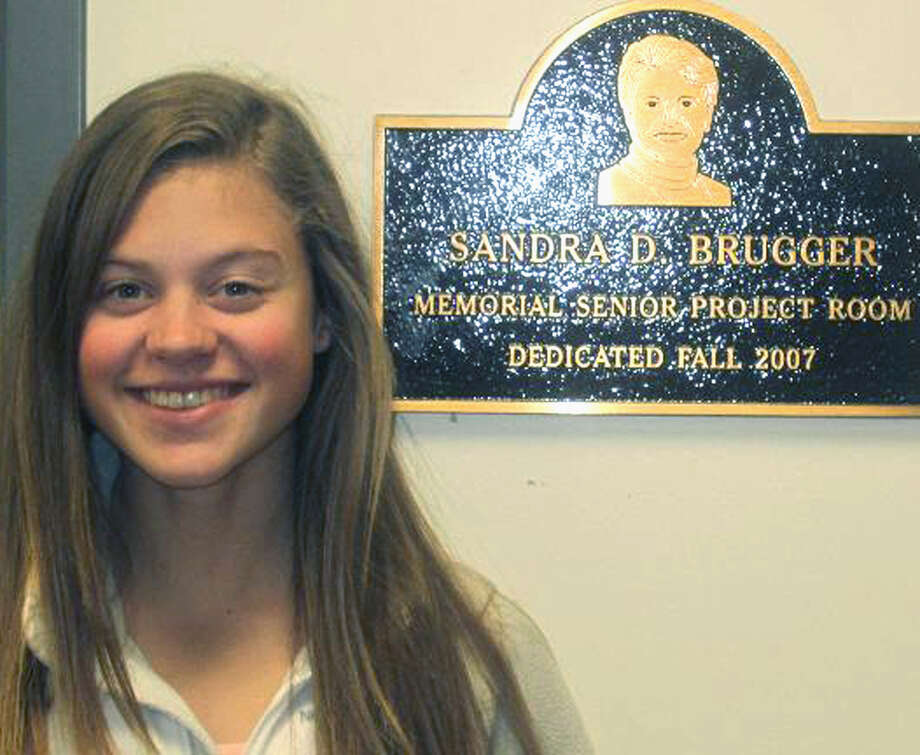 Jessica Dumas of Roxbury has used her senior project at Shepaug Valley High School to help people well beyond the borders of Region 12. She is shown her next to the memorial plaque in the school's senior project room for longtime senior project coordinator Sandy Brugger. Photo: Contributed Photo