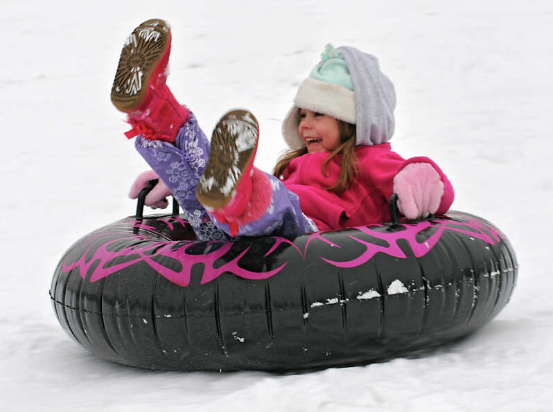 Calli Novak, 4, of Troy smiles while having fun going down a hill on her tube at Frear Park on Wedne