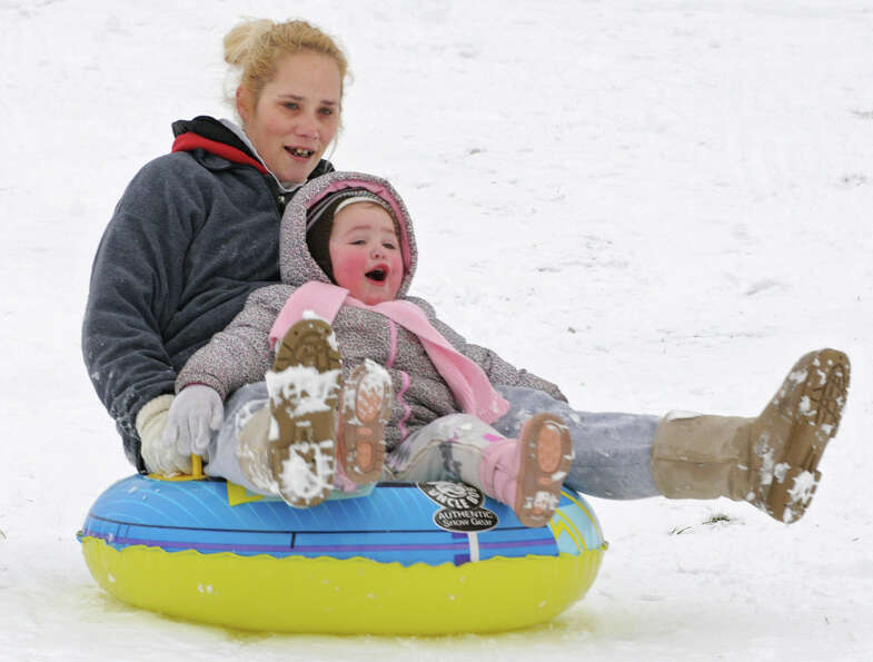 Jen Bendon of Wynantskill takes her 2-yr-old granddaughter Adrianna Wescott down a hill on a tube at