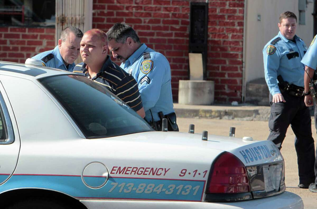 Houston Police officers take a bank robbery suspect into custody after police chase which ended at Scott and Noah streets Wednesday, Jan. 16, 2013, in Houston. The suspects were wanted in connection with bank robbery at the Trustmark Bank located in the 10100 block of the Katy Freeway.
