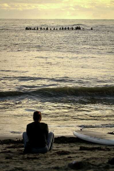 A woman watches from Mavericks Beach during the opening ceremony for the Mavericks Surf Contest in P