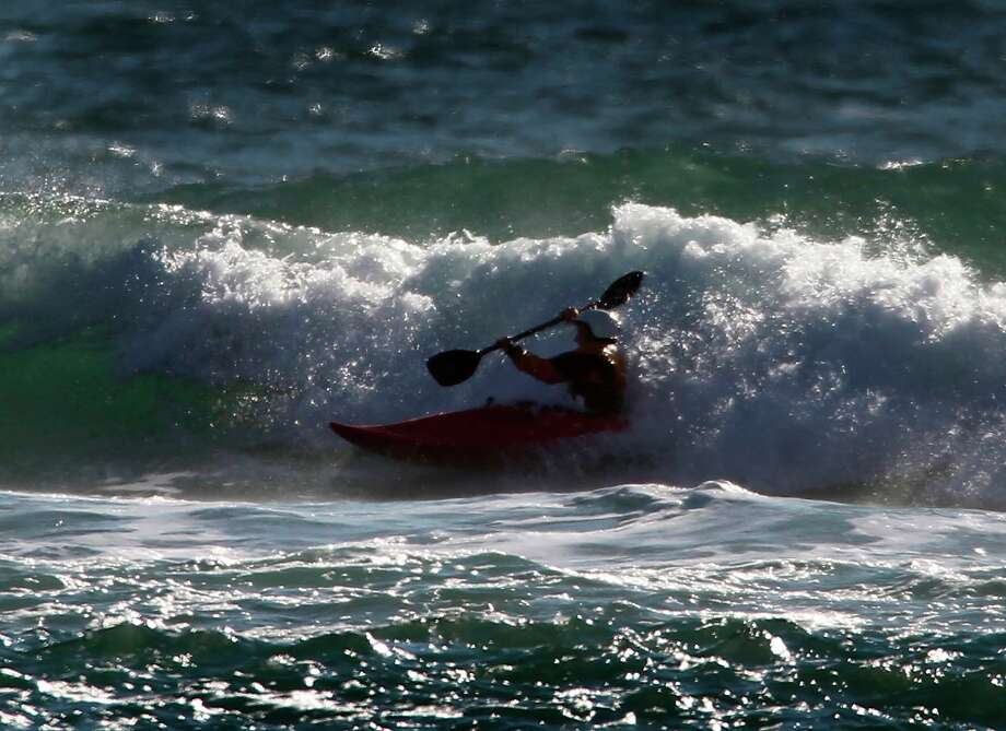 Scott Kazmar guides his surf kayak through a small wave at Mavericks near Pillar Point Harbor on Saturday, Feb. 26, 2011. Mavericks surf contest organizers are ready to cancel this year's competition due to poor conditions. Photo: Paul Chinn, The Chronicle / SFC