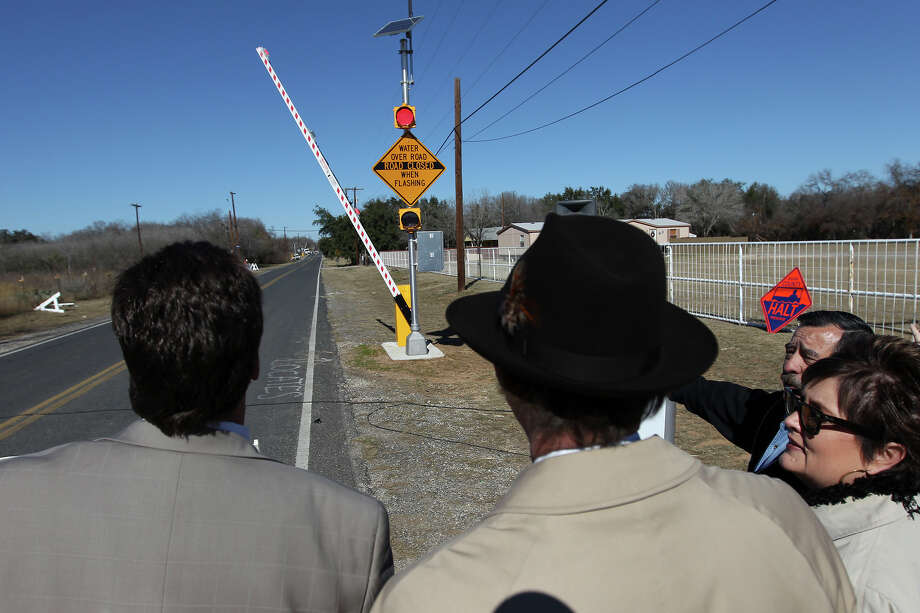 Southwest ISD Superintendent Dr. Lloyd Verstuyft (from left), Bexar County Judge Nelson Wolff and Bexar County Director of Public Works Renee Green join others in watching a demonstration of the county's new $3 million high water detection system on Shepherd Road at Live Oak Creek on Wednesday, Jan. 16, 2013. The system is called the High water Alert Lifesaving Technology (HALT) and features warning lights, audio alerts and a railroad-style arm that are activated to alert motorists whenever a road is flooded. 52 HALT systems will be put to use in Bexar County. Photo: Kin Man Hui, San Antonio Express-News / © 2012 San Antonio Express-News