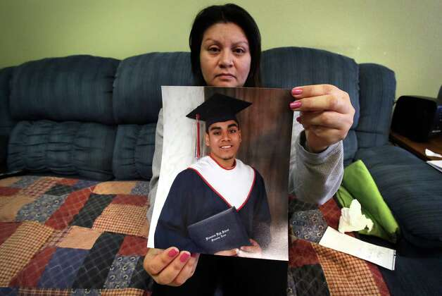 Rachel Enriquez holds a photo of her son Christopher Hinojos (cq), who was gunned down following what police describe as a carjacking murder, Wednesday, Jan. 16, 2013.  A 2012 graduate from Plainview High School, Hinojos had just started a new job and was on is way home when the incident occured. Photo: Bob Owen, San Antonio Express-News / © 2012 San Antonio Express-News