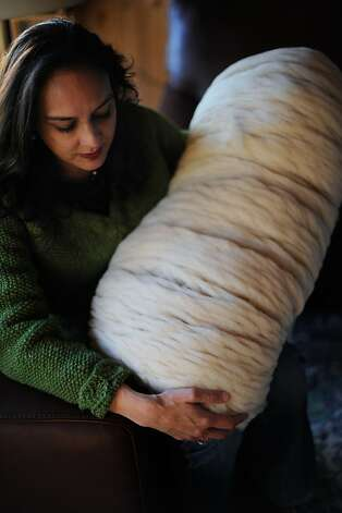 Harmeet Dhillon carries raw wool ready to be spun. Photo: Erik Castro, Special To The Chronicle