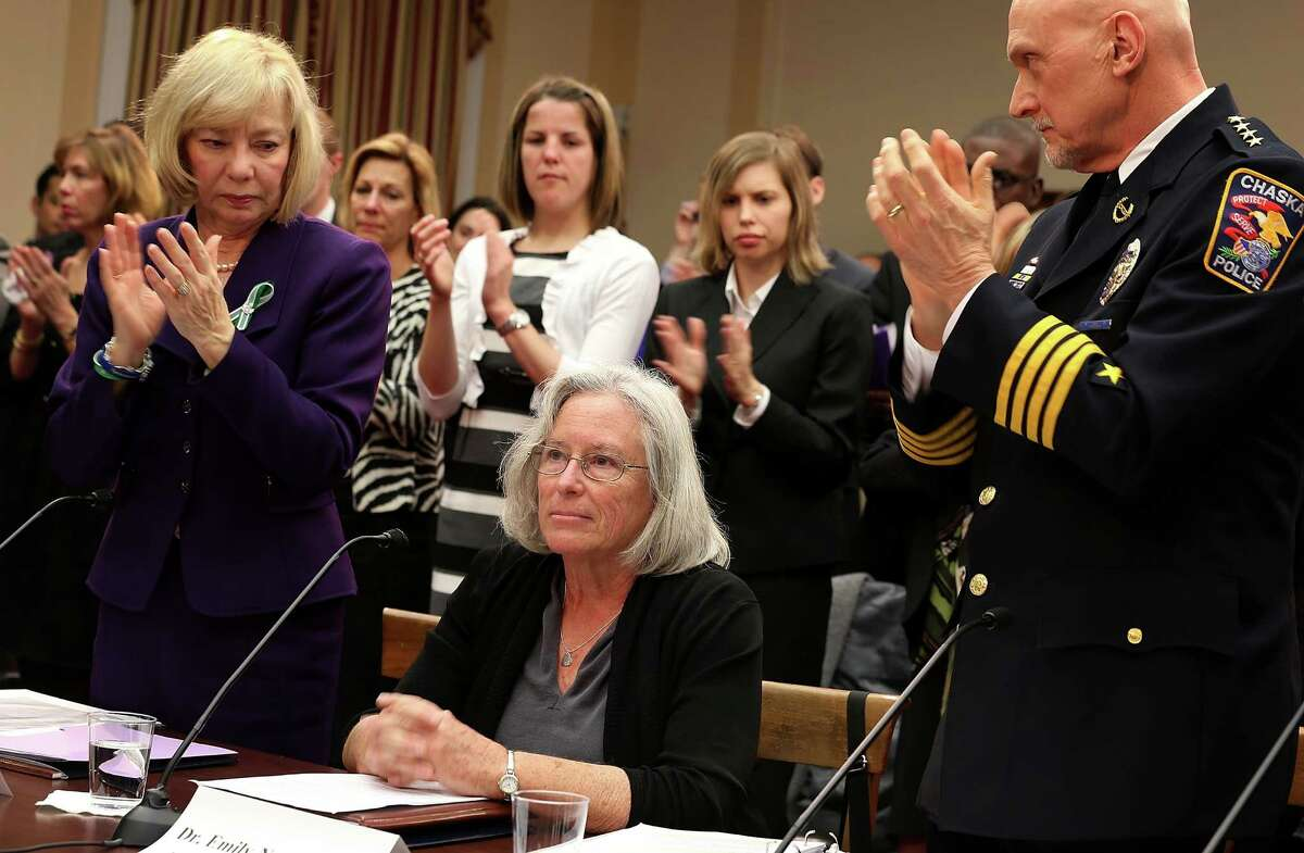 Emily Nottingham (C), mother of Gabe Zimmerman, a staff member to former Rep. Gabrielle Giffords' who was killed during the Tucson, Arizona shootings receives a standing ovation, including from Superintendent of schools of Newtown, Connecticut, Janet Robinson (L) and chief of police for the City of Chaska, Minnesota, Scott Knight (R) during a hearing before the House Democratic Steering and Policy Committee January 16, 2013 on Capitol Hill in Washington, DC. The committee held a hearing to focus on
